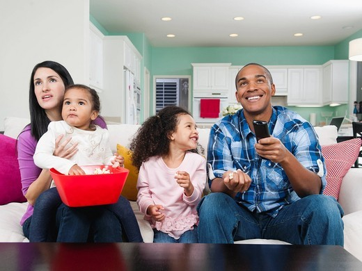 Family sitting on sofa watching television : Stock Photo