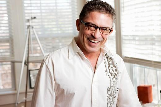 Hispanic artist standing in studio : Stock Photo