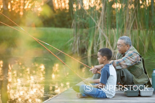 Stock Photo: 1589-142637 Grandfather and grandson fishing on pier