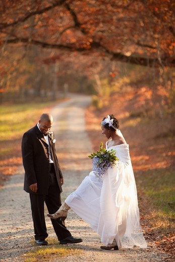African American bride and groom standing on path : Stock Photo