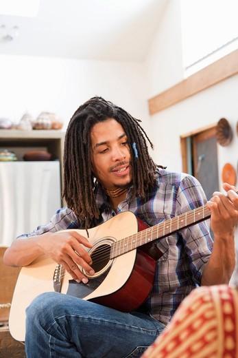 Mixed race man playing guitar : Stock Photo