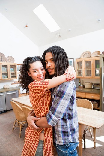 Couple hugging in kitchen : Stock Photo