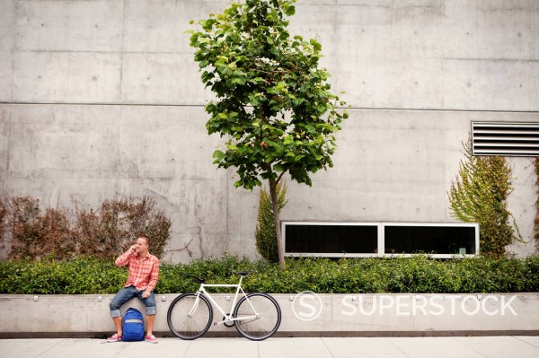 Stock Photo: 1589-142783 Bicycle messenger stopping on city street using cell phone