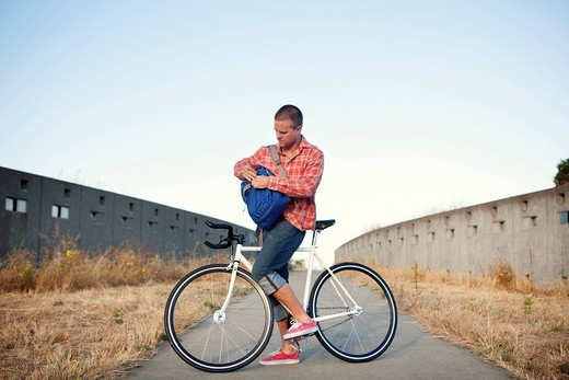 Bicycle messenger stopping on urban path : Stock Photo