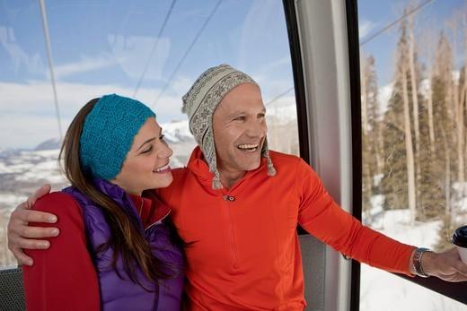 Couple riding in ski gondola together : Stock Photo