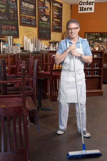 Business owner sweeping cafe floor : Stock Photo