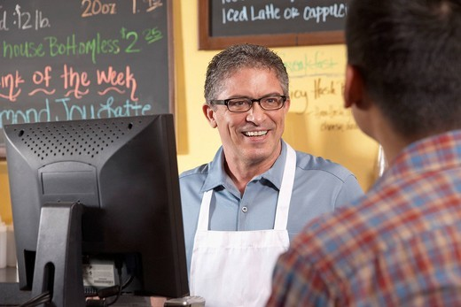Cafe owner serving customer : Stock Photo