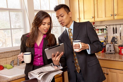 Couple looking at digital tablet in kitchen : Stock Photo