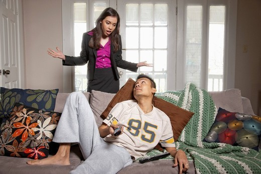 Frustrated wife questioning lazy husband : Stock Photo