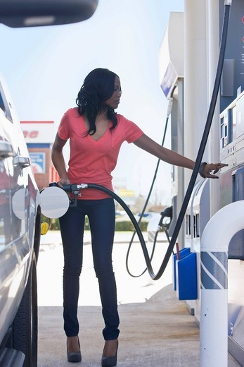 African American woman pumping gas at gas station : Stock Photo