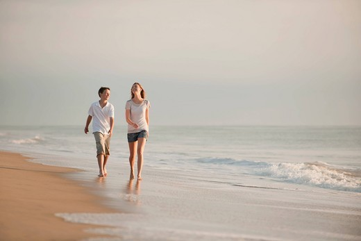 Caucasian brother and sister walking on beach : Stock Photo