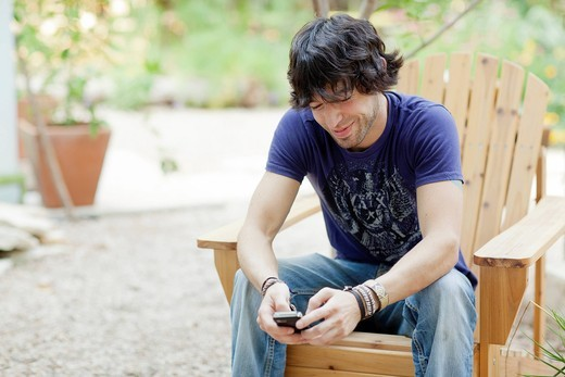 Mixed race man sitting in chair using cell phone : Stock Photo
