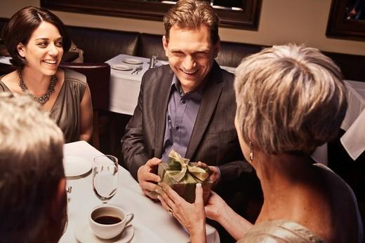 Caucasian man giving woman gift in restaurant : Stock Photo
