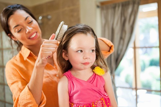 Mixed race mother brushing daughter´s hair : Stock Photo
