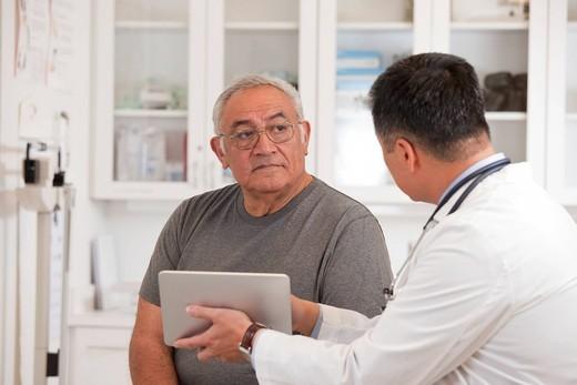 Doctor using digital tablet to talk to senior man : Stock Photo