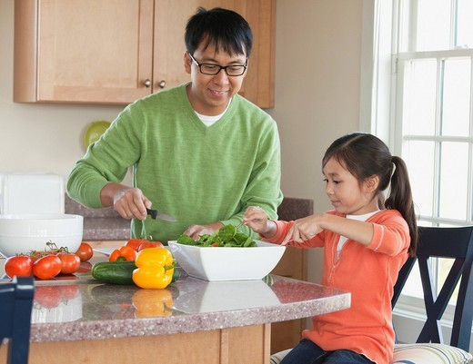 Asian father and daughter preparing a salad : Stock Photo
