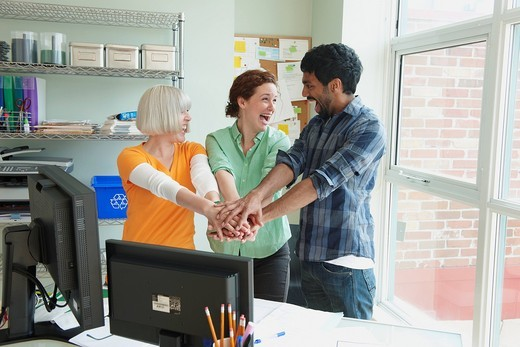 Business people holding hands together in office : Stock Photo