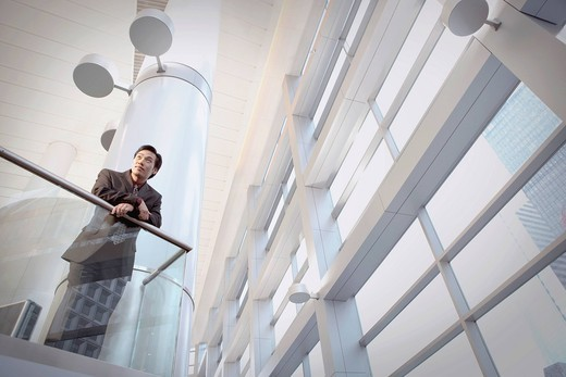 Asian businessman leaning on office railing : Stock Photo