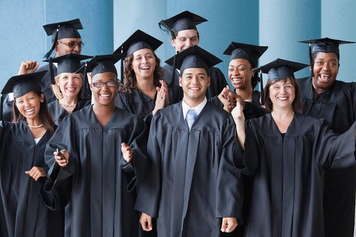 College graduates cheering in caps and gowns : Stock Photo