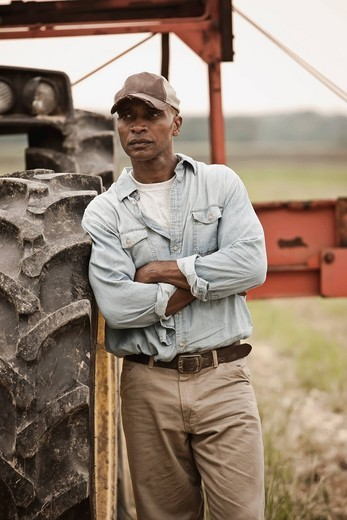 African American farmer standing near tractor : Stock Photo