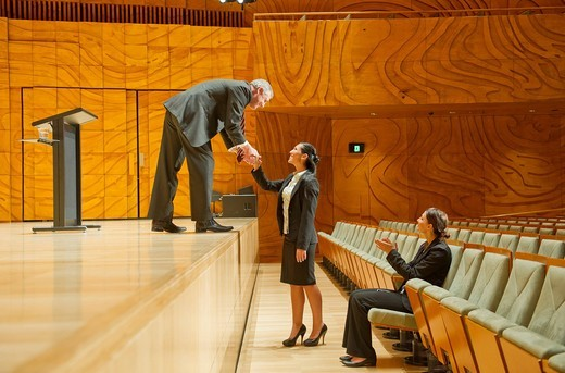 Businessman on stage shaking hands with businesswoman in audience : Stock Photo