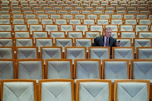Caucasian businessman using cell phone in empty auditorium : Stock Photo