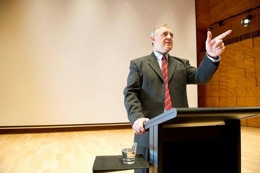 Caucasian businessman making speech at podium : Stock Photo