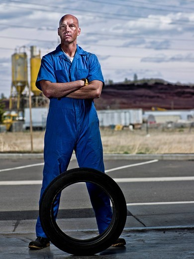Serious mechanic standing with tire : Stock Photo