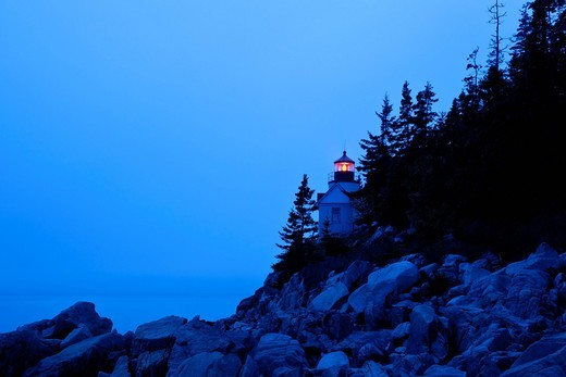 Glowing lighthouse on rocky shore : Stock Photo