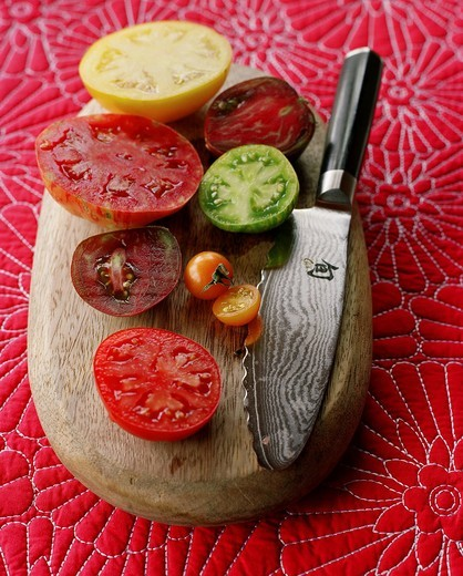 Various juicy sliced tomatoes on cutting board with knife : Stock Photo