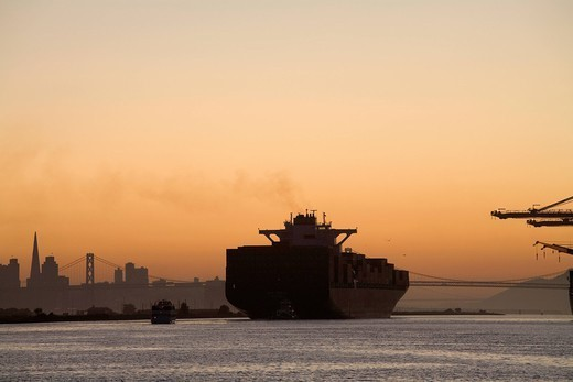 Tugboat and container ship in port of Oakland : Stock Photo