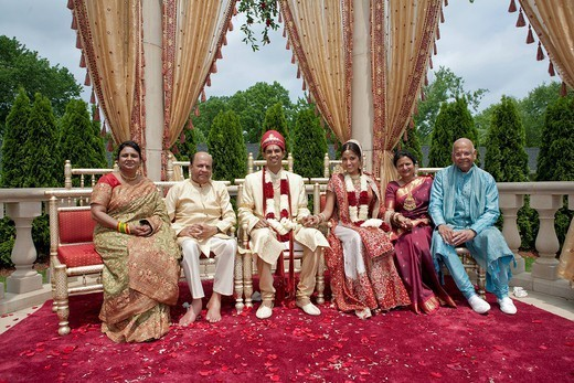 Indian bride and groom with family in traditional clothing : Stock Photo