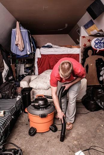 Caucasian man vacuuming floor : Stock Photo