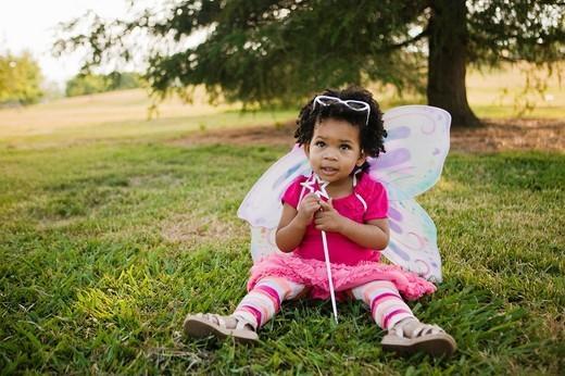 Black baby girl in fairy costume in park : Stock Photo