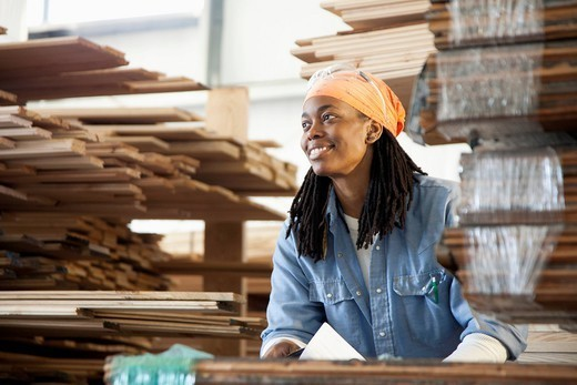 Black worker standing near lumber in warehouse : Stock Photo