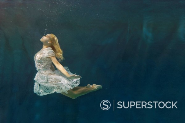 Caucasian woman in dress swimming under water : Stock Photo