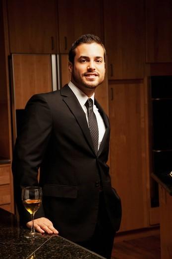 Hispanic man drinking wine in kitchen : Stock Photo