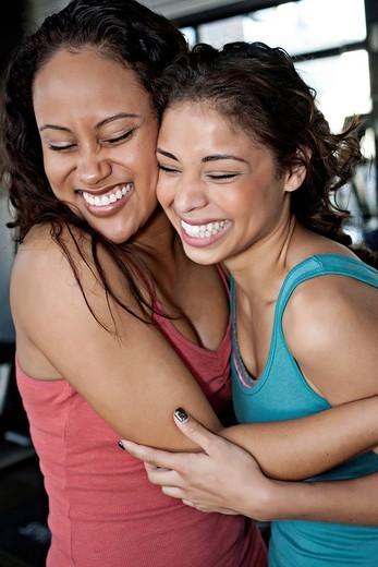 Smiling women hugging in health club : Stock Photo