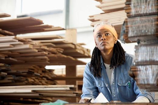Black worker standing near lumber in warehouse : Stock Photo