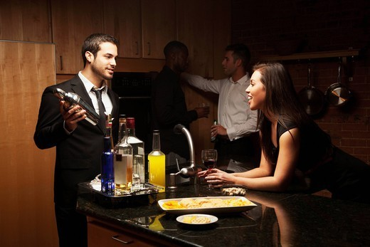 Friends drinking in kitchen at party : Stock Photo