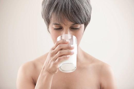 Mixed race woman drinking milk : Stock Photo
