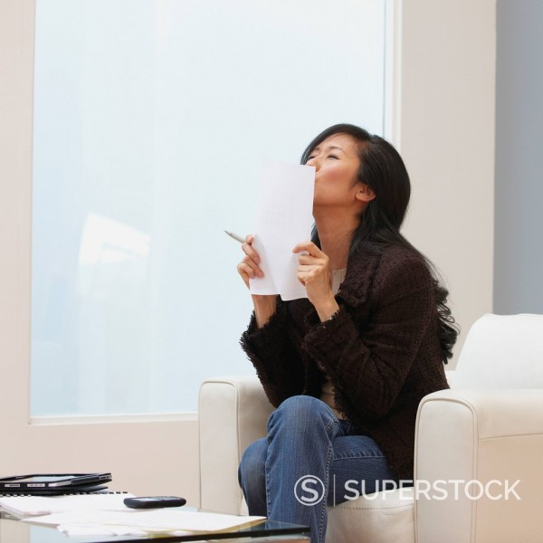 Excited Chinese businesswoman kissing paperwork : Stock Photo