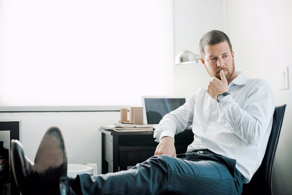 Stock Photo: 1589-161656 Caucasian businessman sitting at desk with feet up