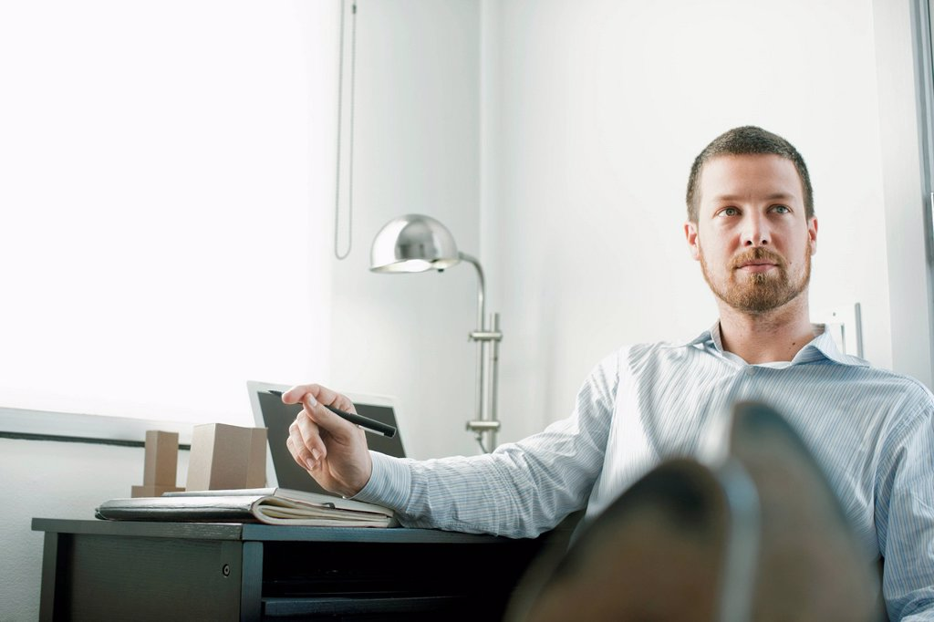 Caucasian businessman sitting at desk with feet up : Stock Photo