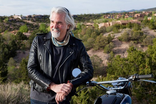 Caucasian man standing with motorcycle : Stock Photo