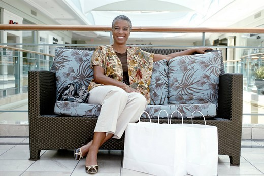 Black woman sitting on sofa in mall with shopping bags : Stock Photo