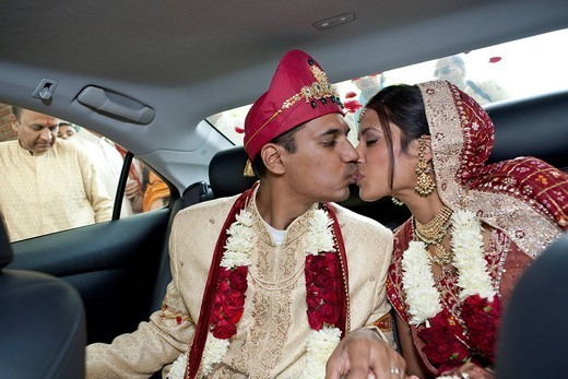 Indian bride and groom in traditional clothing kissing in car : Stock Photo