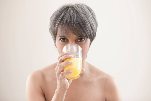 Mixed race woman drinking orange juice : Stock Photo