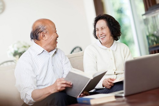 Chinese couple with book and laptop : Stock Photo