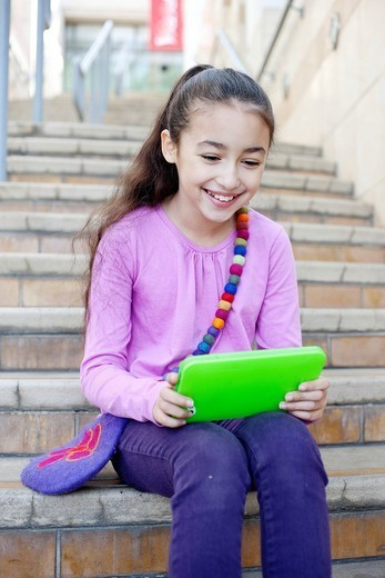 Mixed race girl using digital tablet on staircase : Stock Photo